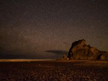 Night sky over Lion rock @ Piha, New Zealand. Night sky filled with thousands of stars over the famous lion rock at Piha beach, New Zealand Stock Photos