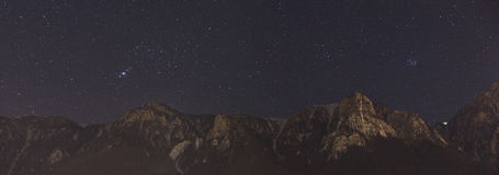 Night sky panorama. Constellations Orion, Taurus and Pleiades over Bucegi mountains Royalty Free Stock Image