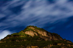 The night sky. Peaks on the night sky, white clouds and stars Royalty Free Stock Photography