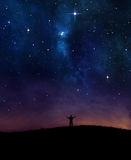 Night sky praise. A man lifting his hands in praise under night sky stock image