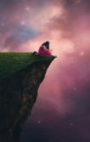 Night sky prayer. A woman praying on top of a cliff before the night sky Royalty Free Stock Photography
