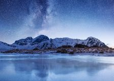 Night sky and reflection on the frozen lake. Natural landscape in the Lofoten islands, Norway. Natural night landscape at the winter time stock image