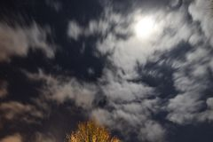 Night sky scene with moving clouds lighted by the moonlight. Night sky scene with moving clouds and star spots lighted by the moonlight royalty free stock photo