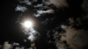 Night sky with shining full moon behind moving dramatic clouds. Time lapse stock footage