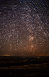 night sky, spiral star trails and the forest Royalty Free Stock Images