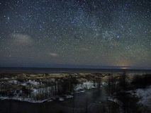 Night sky stars and snow on sea coast stock photo