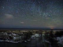 Night sky stars and snow on sea coast. Night sky stars and clouds over Baltic sea, snow and trees on sea coast stock photo