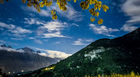 Night sky stars and clouds over mountain. Night sky stars and clouds with mountain background royalty free stock photo