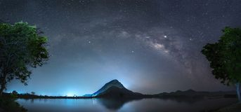 Night sky with stars and The Milky Way is above the mountain and reflection on the water. Lam Isu Reservoir Kanchanaburi, Thailand stock photo
