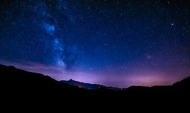 Night sky stars milky way blue purple sky, starry night. Night sky stars milky way blue purple sky in starry night over mountains Stock Photography