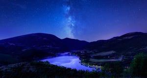 Night sky stars on mountain lake. Milky way reflections in dark Stock Photos