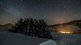 Night sky with stars moving over winter rural country with wooden frame, astronomy time lapse, dolly shot over snow. Timelapse video of beautiful winter night stock video