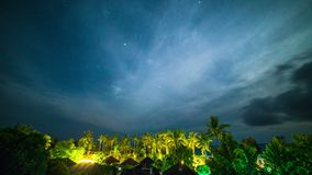 Night sky time-lapse of with stars over the rainforest, palms and bungalows on Bali island in Indonesia. 4K Timelapse in Bali Island, indonesia stock footage