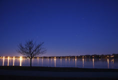 Night Sky Turns to Morning. The night sky fades to morning light and Orion the Hunter begins to sink to the horizon, below the city lights, and the frozen lake Royalty Free Stock Images