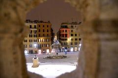 Night snowfall on empty Spanish square and steps in Rome with church Trinita di Monti in background, Italy. Piazza di Spagna. Blizzard stock image