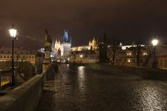 Night colorful snowy Christmas Prague Lesser Town with gothic Castle with Charles Bridge, Czech republic Royalty Free Stock Images