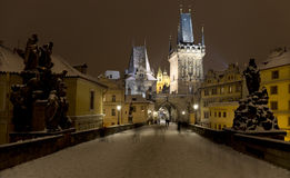 Night snowy colorful  Prague Lesser Town with Bridge Tower and St. Nicholas` Cathedral from Charles Bridge, Czech republic Stock Photos