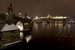 Night snowy colorful Prague Lesser Town with gothic Castle, St. Nicholas` Cathedral and Charles Bridge, Czech republic Stock Photos