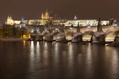 Night snowy colorful Prague Lesser Town with gothic Castle, St. Nicholas` Cathedral and Charles Bridge, Czech republic Royalty Free Stock Photos