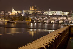 Night snowy colorful Prague Lesser Town with gothic Castle, St. Nicholas` Cathedral and Charles Bridge, Czech republic Royalty Free Stock Images