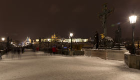 Night snowy colorful Prague Lesser Town with gothic Castle, St. Nicholas` Cathedral from Charles Bridge, Czech republic Stock Photography