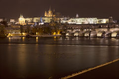 Night snowy colorful Prague Lesser Town with gothic Castle, St. Nicholas` Cathedral from Charles Bridge, Czech republic Royalty Free Stock Image