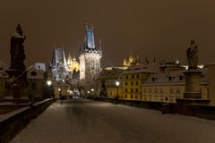 Night snowy colorful Prague Lesser Town with gothic Castle, St. Nicholas` Cathedral from Charles Bridge, Czech republic Royalty Free Stock Photos