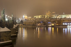 Night snowy Prague gothic Castle with Charles Bridge and St. Nicholas' Cathedral , Czech republic Stock Image