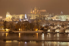 Night snowy Prague gothic Castle with Charles Bridge and St. Nicholas' Cathedral , Czech republic Stock Images