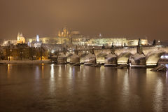 Night snowy Prague gothic Castle with Charles Bridge and St. Nicholas' Cathedral , Czech republic Stock Photo