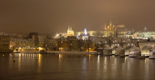 Night snowy Prague gothic Castle with Charles Bridge and St. Nicholas' Cathedral , Czech republic Royalty Free Stock Photos