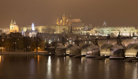 Night snowy Prague gothic Castle with Charles Bridge and St. Nicholas' Cathedral , Czech republic Royalty Free Stock Photo