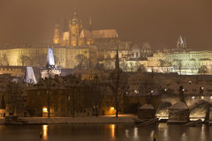 Night snowy Prague gothic Castle with Charles Bridge and St. Nicholas' Cathedral , Czech republic Stock Photos