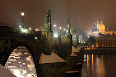 Night snowy Prague gothic Castle and St. Nicholas' Cathedral with Charles Bridge, Czech republic Royalty Free Stock Photography