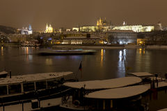 Night snowy Prague Lesser Town with gothic Castle, above River Vltava, Czech republic Royalty Free Stock Photo