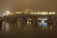Night snowy Prague Lesser Town  with gothic Castle, Bridge Tower and St. Nicholas' Cathedral and Charles Bridge Royalty Free Stock Photo
