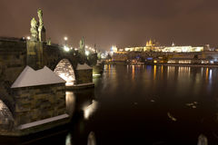 Night snowy Prague Lesser Town with gothic Castle, St. Nicholas` Cathedral and Charles Bridge, Czech republic Stock Photography