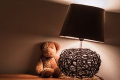 Night stand with teddy and lamp stock images