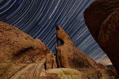 Night Star Trail Streaks over the Rocks of Joshua Tree Park Stock Photos