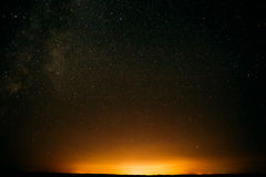 Night Starry Sky Above Field And Yellow Lights On Background. Night Royalty Free Stock Image