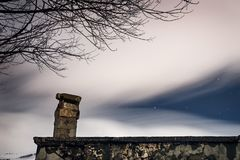 Night starry sky. Under a veil of white smoky clouds over the roof of an old abandoned house, beautiful nature near old decrepit building Royalty Free Stock Photos