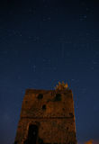 Night starry sky over an abandoned stone tower. A falling star is visible. A deep dark night. Stock Photos