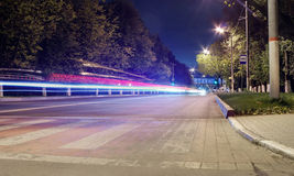 Night street. Street by night with street illumination, traffic light and cars passing Royalty Free Stock Photo