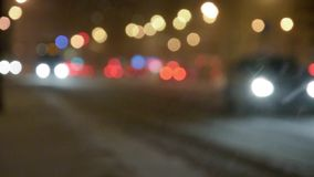 Night street with bokeh lights in the snowstorm. stock video footage