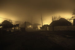 Night street country road with buildings and fences covered in fog lamp . Or Mysterious night in the centre of Ilisu village Gakh,. Azerbaijan Royalty Free Stock Photos