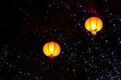 On the night street, I saw a big tree decorated with sparkling blue lights and two warm red lanterns. stock images