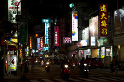 Night street in Kaohsiung. People riding motorbikes in the night at a crowded street filled with small restaurants in Kaohsiung, Taiwan Royalty Free Stock Photos