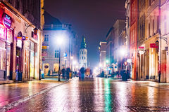 Night street in the Krakow, Poland. Colorful night illumination reflecting in the wet stone pavement of the old town. Beautiful background photo royalty free stock image