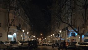 Night street lined with trees lanterns and parked cars. Valencia, Spain. VALENCIA, SPAIN - JANUARY 13, 2018: Night cityscape. Street view with parked cars and stock footage