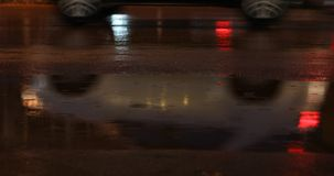 Night street in the rainy weather day with car driving on asphalt road. Night street in the rainy weather day, rain drop on puddle water with car driving on stock footage
